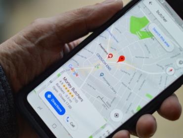 Bild mit einer Hand, die ein Handy hält auf de Google Maps geöffnet ist