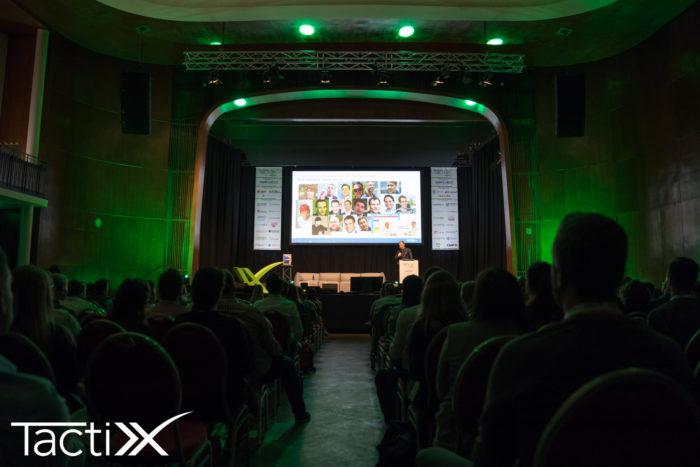 Zu sehen ist ein Vortrag auf der TactixX, aus dem Publikum heraus fotografiert