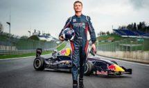 Zu sehen ist Davis Coulthard vor einem Rennwagen mit Helm unterm Arm