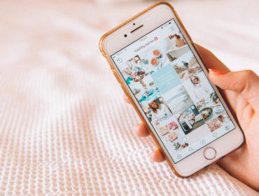 Jemand hält ein Smartphone in der Hand. Auf diesem ist ein Instagram Profil zu sehen.