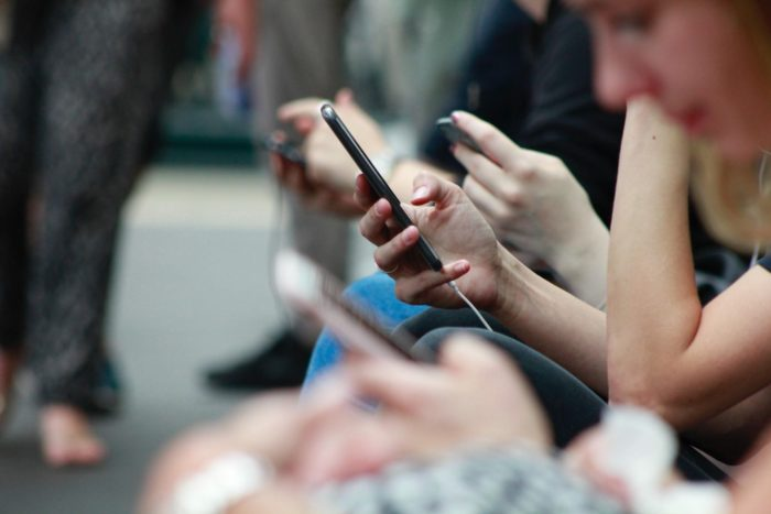 Das Bild zeigt mehrere Personen, die sitzend auf ihr Smartphone sehen