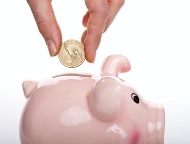 Sparschwein, in das eine Münze gesteckt wird