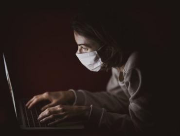 Bild Mann mit Maske vor einem Computerbildschirm