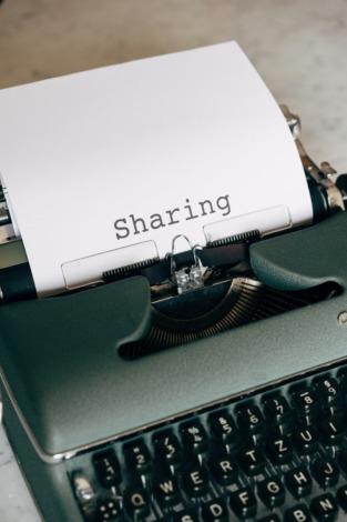 """Bild einer Schreibmaschine mit dem Wort """"Sharing"""" auf einem Blatt Papier"""